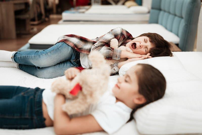 Little happy girl hugs bear lying on bed. In background little boy sleeps. royalty free stock image
