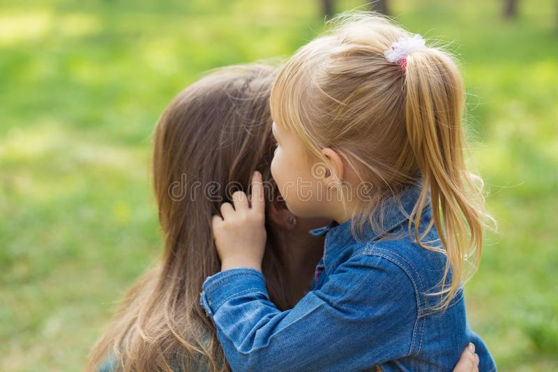 Little happy girl hugs her mom and tells her something in the ear in the park royalty free stock photo