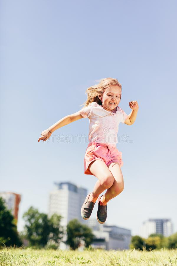 Little happy girl jumping high on the meadow. stock images