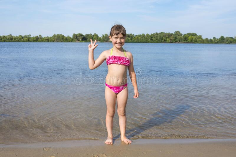 A little happy girl in a pink bathing suit standing on the bank of a river on a sunny summer day.  Beach season royalty free stock images