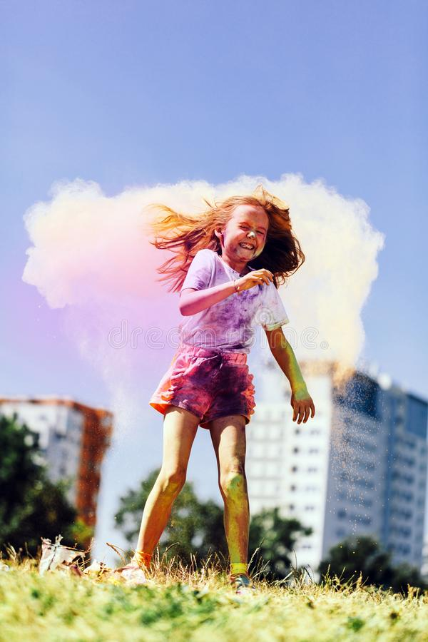 Little happy girl playing with colorful holi powder stock photo
