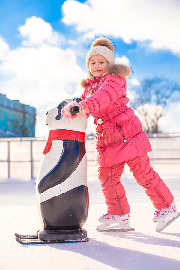 Little happy girl skating on the ice-rink. This image has attached release stock photos