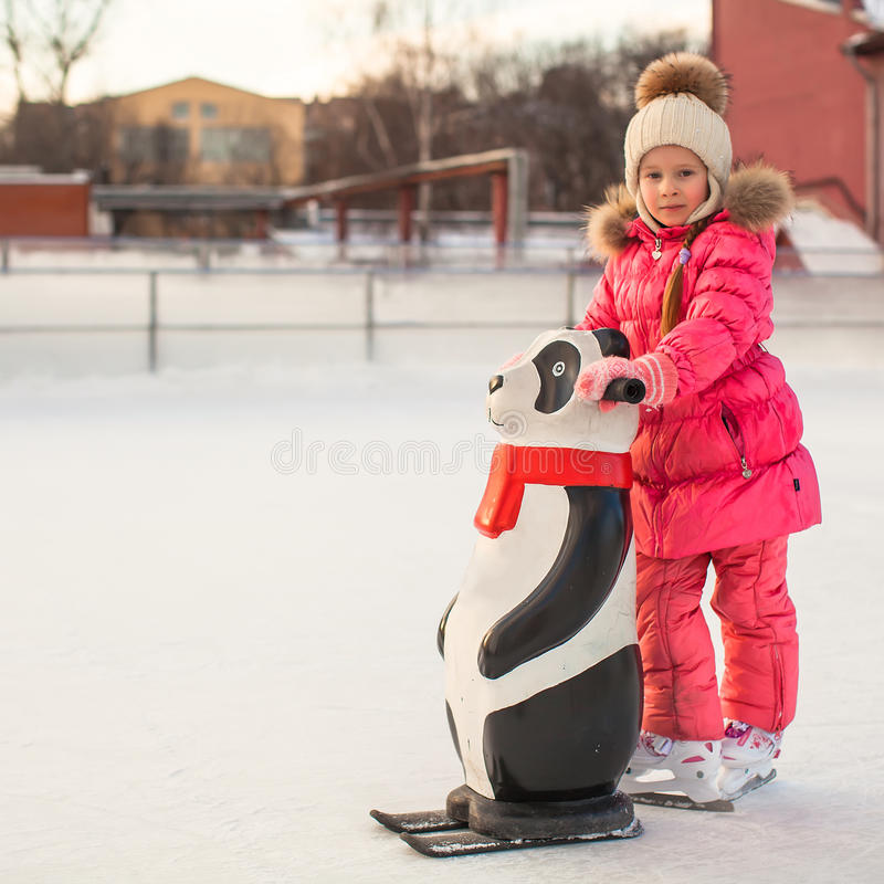 Little happy girl skating on the ice-rink. This image has attached release royalty free stock image
