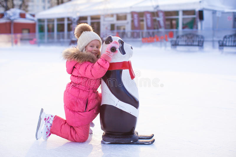 Little happy girl skating on the ice-rink. This image has attached release royalty free stock photos