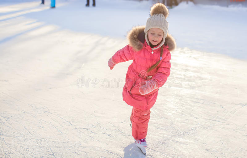 Little happy girl skating on the ice-rink. This image has attached release stock photo