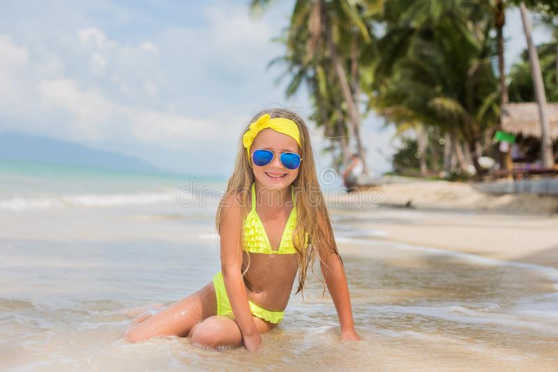 Little happy girl in sunglasses and a swimsuit in the sea. Concept of relaxation and vacation stock photography
