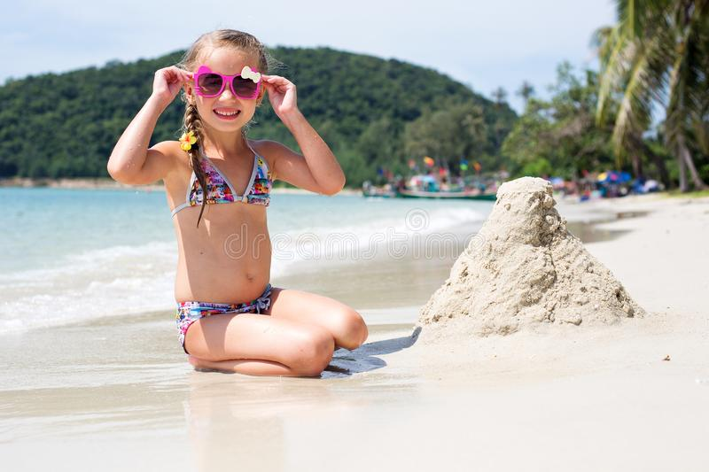 Little happy girl in sunglasses and a swimsuit in the sea. Concept of relaxation and vacation.Girl playing sand on the seashore royalty free stock image