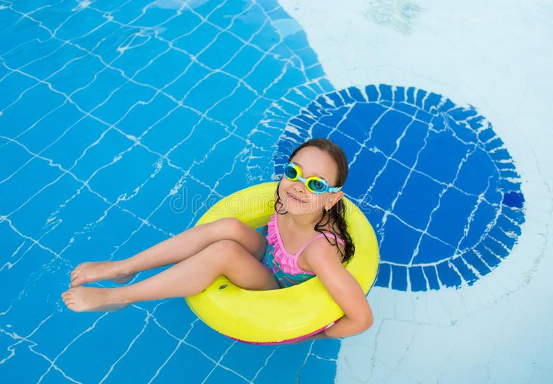 Little happy girl swimming in the outdoor pool on an inflatable yellow circle with diving glasses on a Sunny summer day stock photos