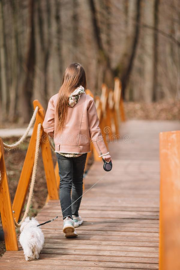 Little girl with a white puppy. A puppy in the hands of a girl. Little happy girl walking with white puppy outdoors in early spring royalty free stock images