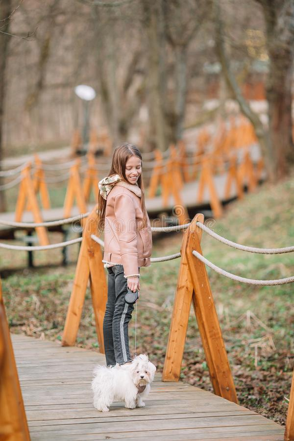 Little girl with a white puppy. A puppy in the hands of a girl. Little happy girl walking with white puppy outdoors in early spring royalty free stock photography