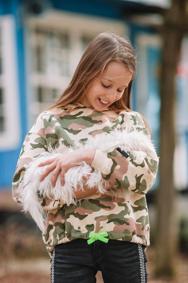 Little girl with a white puppy. A puppy in the hands of a girl. Little happy girl with white puppy outdoors. She is very happy to play with her pet stock photos