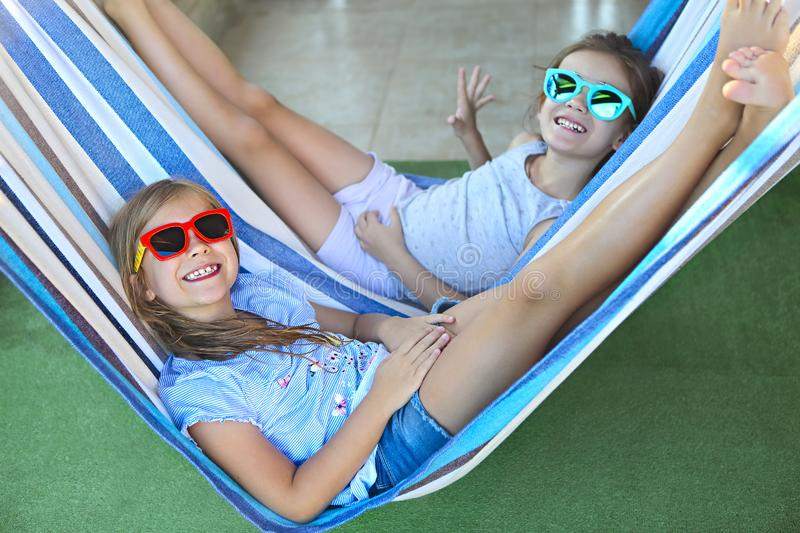 Little happy girls playing on hammock in summer day royalty free stock photos