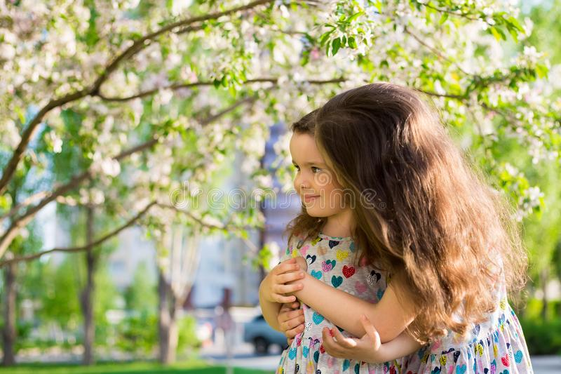 Little happy girls on a walk on a summer evening at sunset in the park. Sisters royalty free stock photos