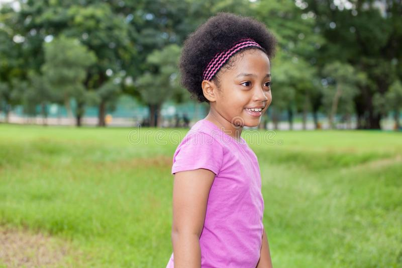Little happy and joyful African American girl playing in the park. royalty free stock photos