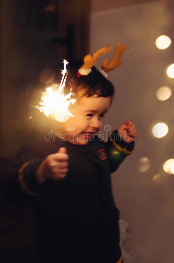 Little kid holding sparkle stick, dancing with joy royalty free stock images