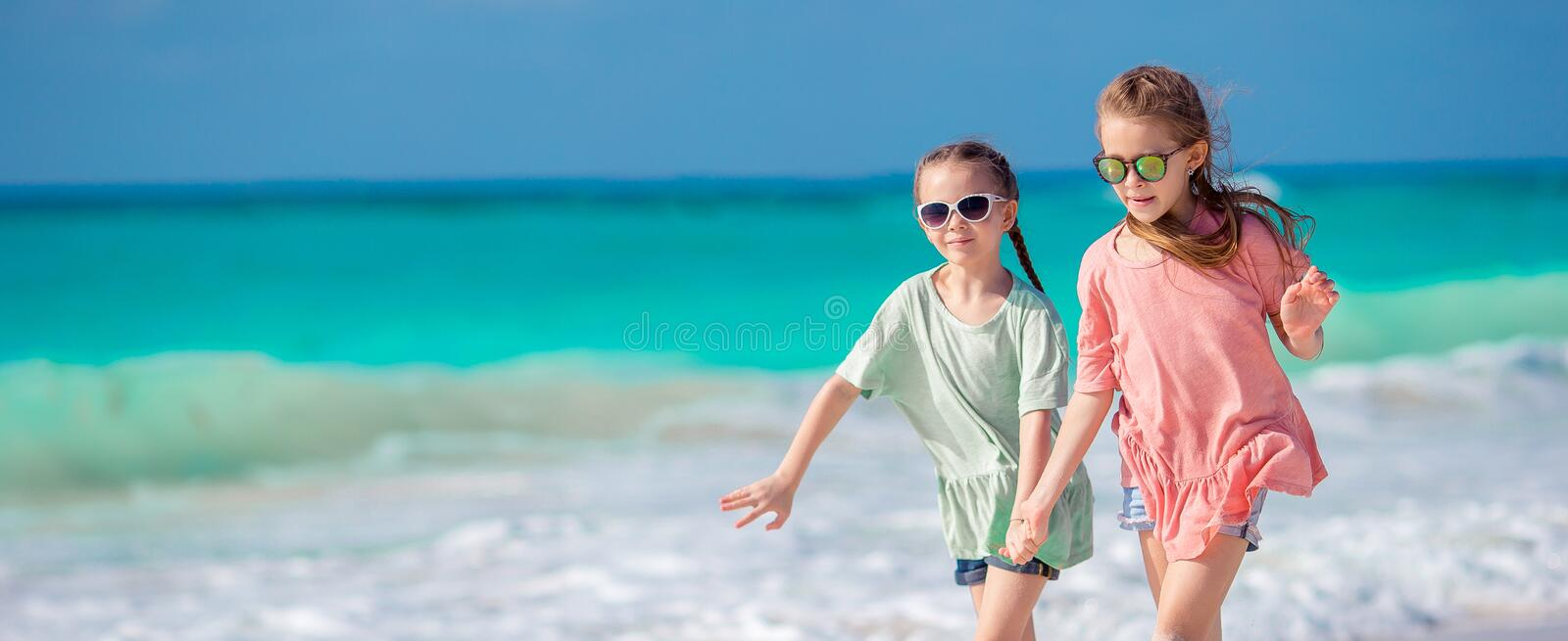 Little happy kids having a lot of fun at tropical beach playing together. Adorable girls dancing on caribbean island royalty free stock photos