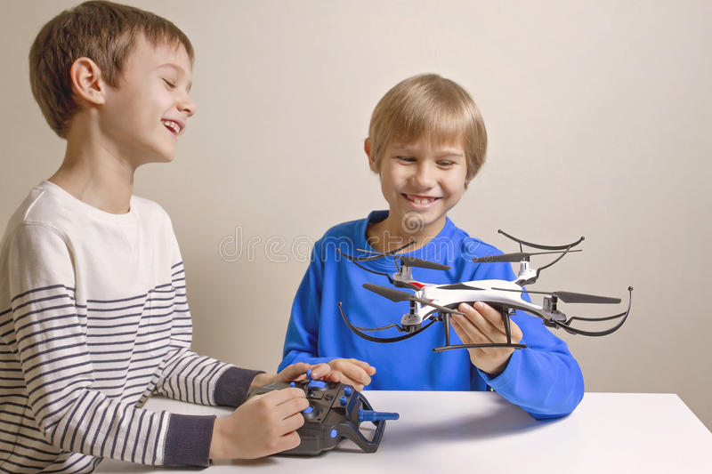 Little happy kids playing with the quadcopter drone at home. stock photo