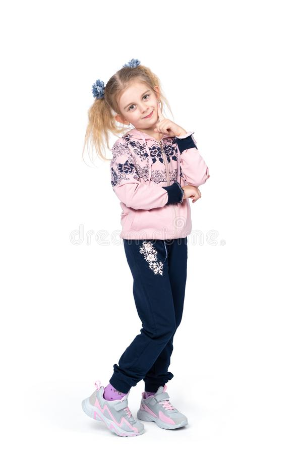 Little happy smiling girl posing in sportswear and sneakers, isolated on white background. royalty free stock photography