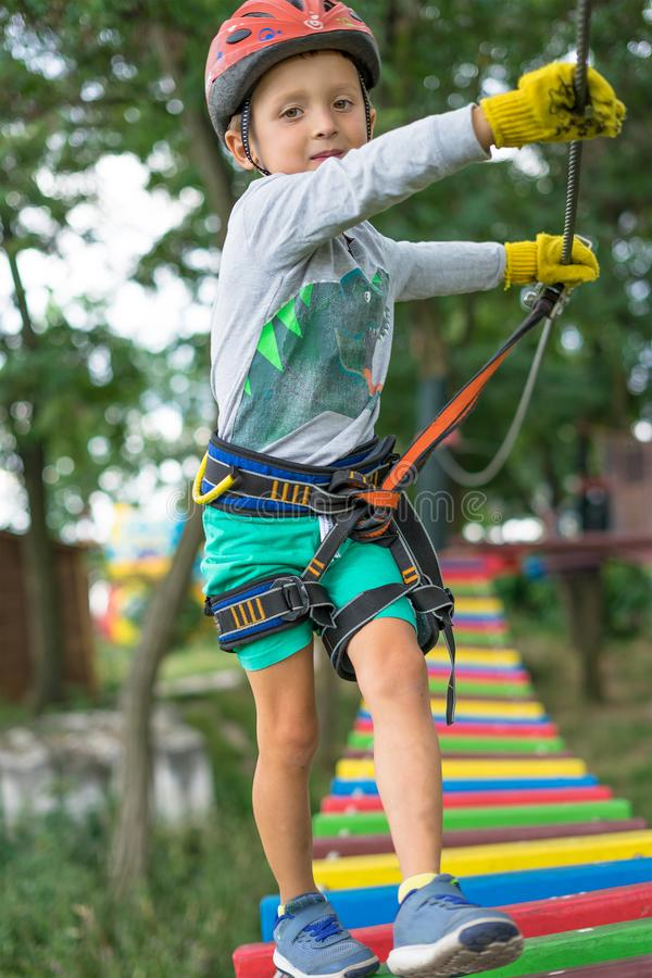 A little happy and smiling rock climber tie a knot on a rope. A person is preparing for the ascent. The child learns to tie a knot stock photo
