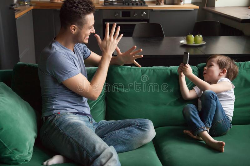 Little boy, son taking photo of funny father on phone royalty free stock photo