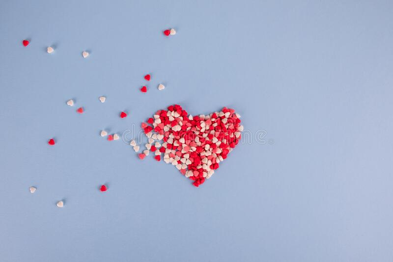 Little hearts pastry sprinkles in the shape of a heart flying on pastel blue background. Valentines day, Mothers day stock images