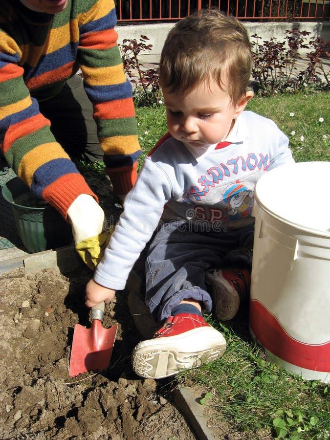 Little help gardener. A little baby boy helps his grandmother in garden works stock images