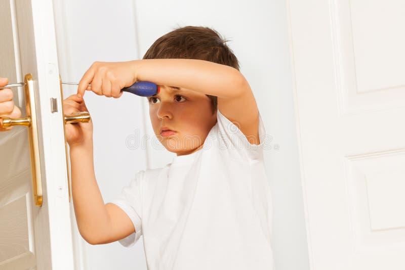 Little helper fixing door handle using screwdriver. Portrait of little helper, six years old boy, fixing door handle using screwdriver at home royalty free stock images