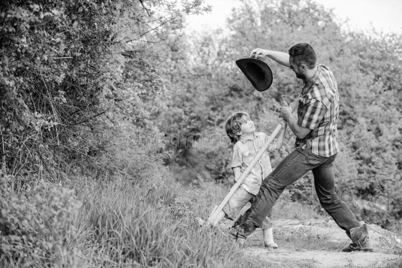 Little helper in garden. Cute child in nature having fun cowboy dad. Find treasures. Little boy and father with shovel stock photo