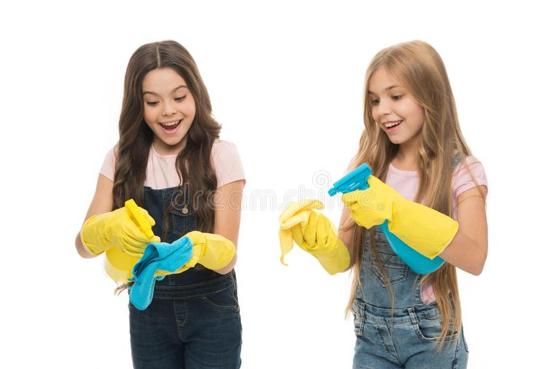 Little helper. Girls cute kids cleaning around with mist sprayer. Keep it clean. Sisters rivalry. Who did better. Girls. With yellow rubber protective gloves royalty free stock images