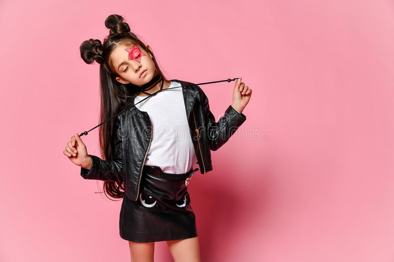 Little hipster girl in a black leather jacket posing on a pink background, holding the ties from the necklace. stock image