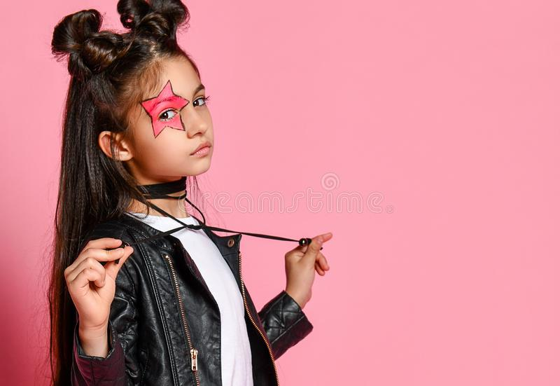 Little hipster girl in a black leather jacket posing on a pink background, holding the ties from the necklace. stock images