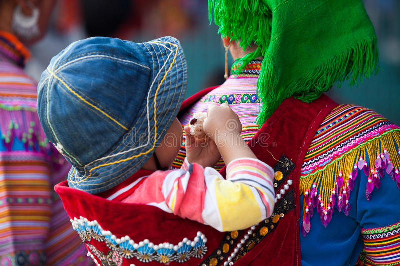 A little Hmong (Miao) child on his mother back coming down to town royalty free stock photo