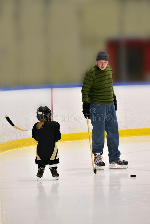 Little hockey girl is wearing in full equipment: helmet, glows, skates, stick. She is hold. Ing a stick and looking on a coach. Coach is explaining something royalty free stock photo