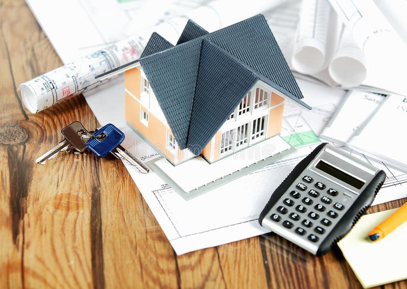 Little Home on Blueprints with Keys and Calculator. Close up View of Conceptual Miniature Model Home on Top of Blueprints, Placed on a Wooden Table, with Keys stock image