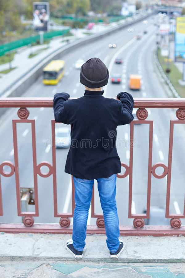 Little homeless boy on the street. Poverty, city royalty free stock image