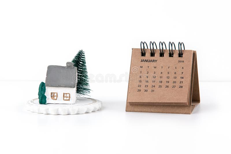 Little house model and tree on white background with calendar 2018 and month of January stock photos