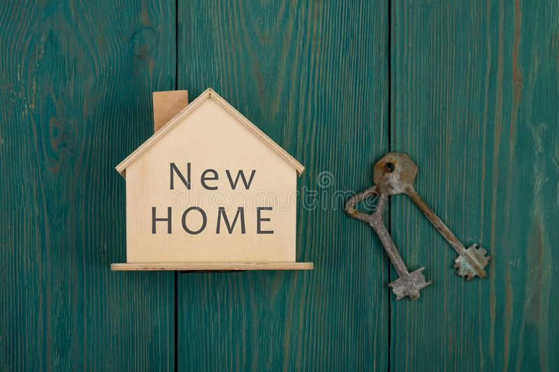 little house with text & x22;new home& x22; and key on blue wooden desk royalty free stock photography