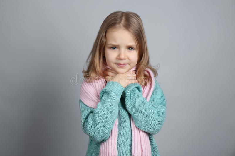 Little ill girl with sore throat on color background stock photography