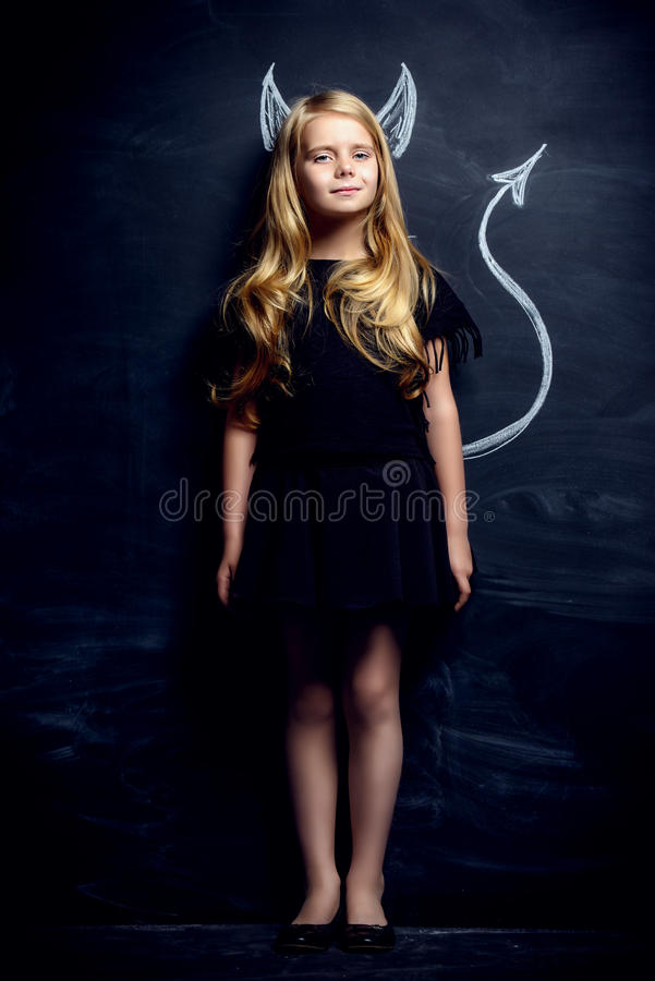 Little imp girl. Funny little imp girl. Cute child girl posing with imp horns and tail drawn on a blackboard stock photo