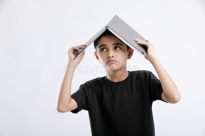little Indian / Asian boy with book on head and thinking seriously royalty free stock photos
