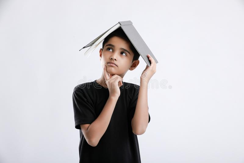 little Indian / Asian boy with book on head and thinking seriously royalty free stock photo