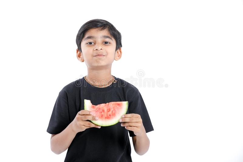 Little Indian boy eating watermelon with multiple expressions.  stock photography