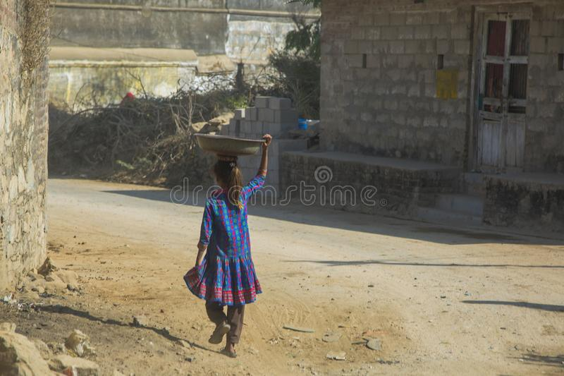 Life in India: Little Girl Carrying Bowl on Head royalty free stock image