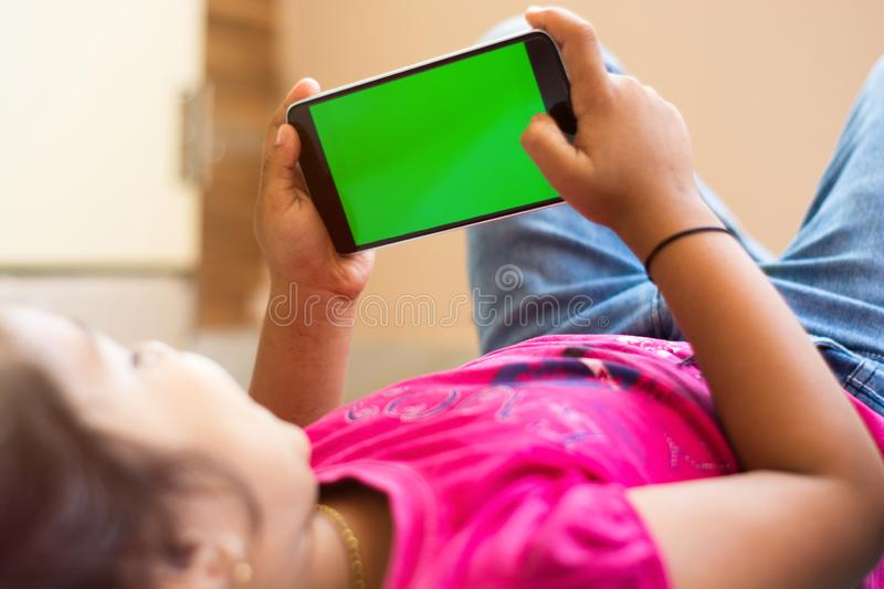 Little Indian Kid with phone in her hands sleeping on bed, mock up with green screen, focus on phone. Little Indian Kid with phone in her hands sleeping on bed stock photography