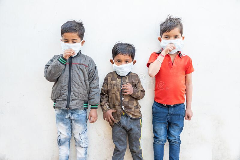 Little Indian Kids wearing surgical mask coughing as they are infected from Coronavirus,originating in Wuhan, China royalty free stock image
