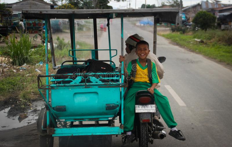 A little Indonesian boy rides a tuk-tuk and laughs merrily stock photo