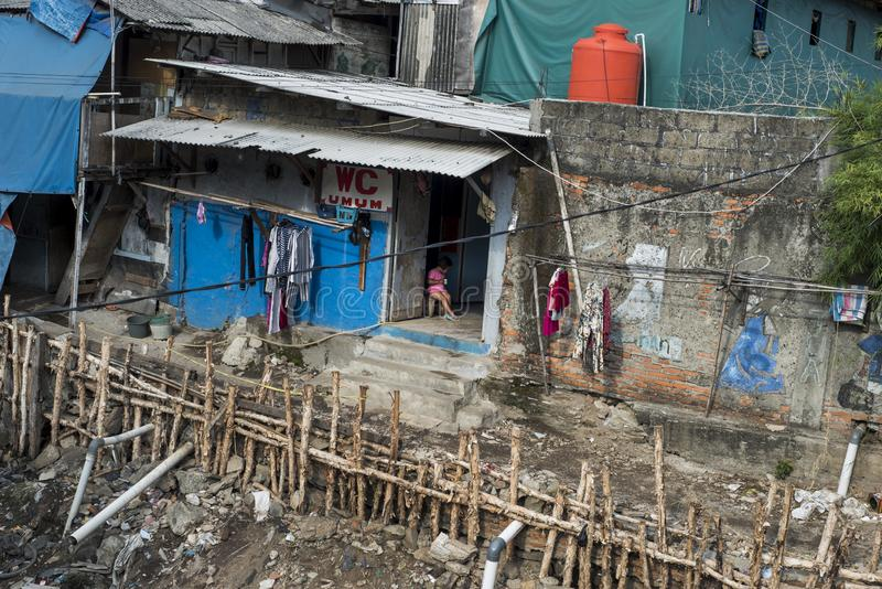 Little Indonesian girl seats by the entrance to the toilets in a slum in Jakarta, Indonesia stock images