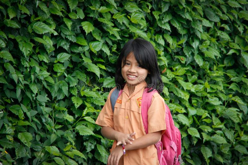 Little Indonesian schoolgirl walks with a school bag against a background of a wall with plants stock photos