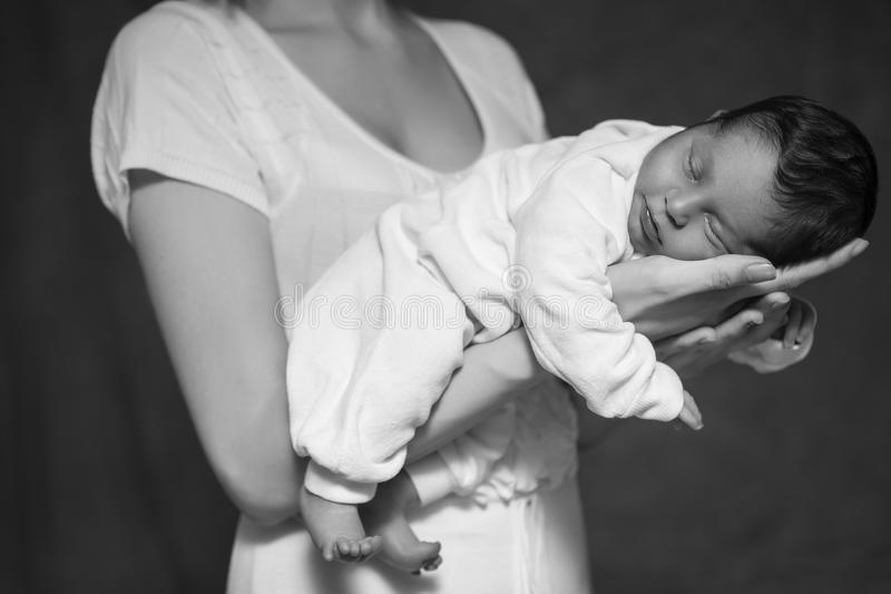 Little infant baby boy sleeping laying on mothers arms. Focus on. A boy. Neutral black background, black and white picture. All in white clothes. Happy family stock photo