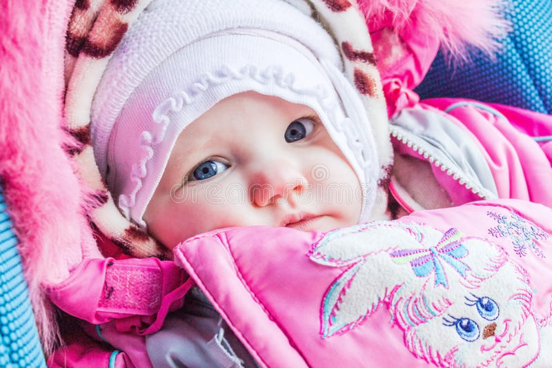 Little an infant girl in winter clothes, face closeup. stock image